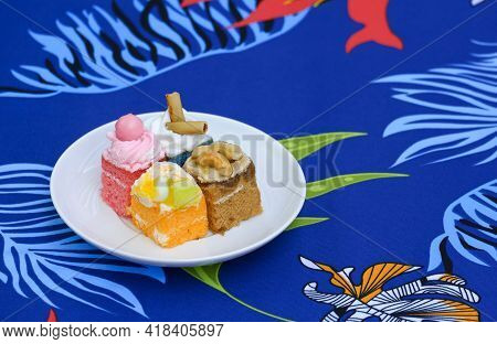 4 Mini Cakes In White Dish On Colorful Foliage Pattern Of Tablecloth