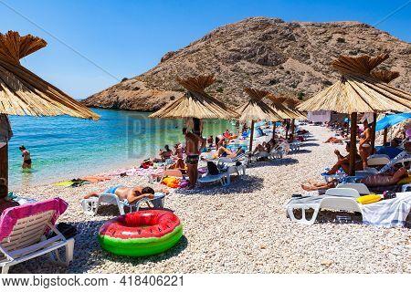 Stara Baska, Croatia - July, 21: Bathers Under The Straw Umbrellas In The Beautiful Oprna Beach On J
