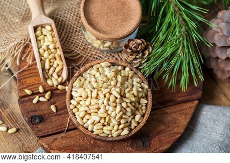 Pine Nuts In A Bowl, Pine Cone, Branch, Glass Jar On A Cutting Board. Still Life From Natural Ingred
