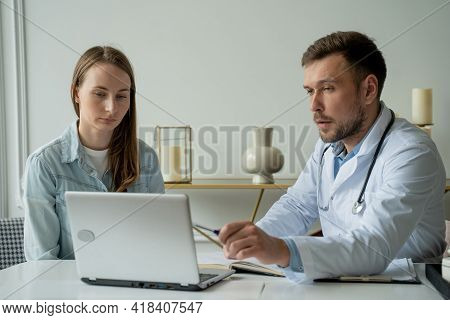 Therapist Doctor Man Talking To Patient. Adult Male In White Coat Talks To Female Patient In Medical