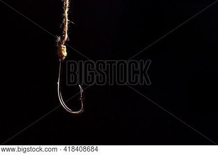 Empty Fishing Hook On A Dark Background. Metal Fishing Hook.