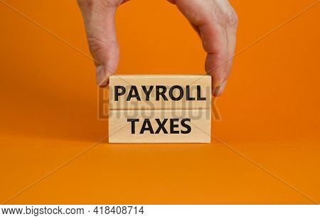 Payroll Taxes Symbol. Wooden Blocks With Words 'payroll Taxes' On Beautiful Orange Background. Busin