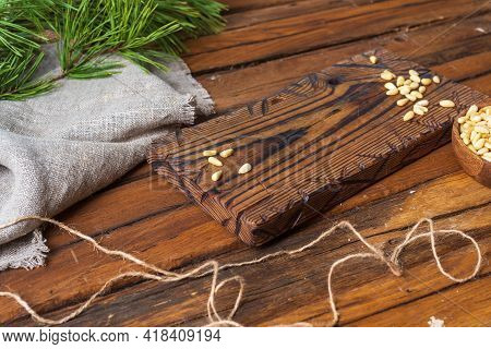 A Wooden Cutting Board On The Table, Peeled Pine Nuts Are Sprinkled On Top, Linen Cloth And A Pine B