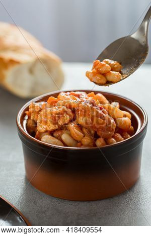 Pork Stew With White Beans In A Brown Bowl.