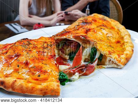 Delicious pizza calzone, with ham, mozzarella and vegetables