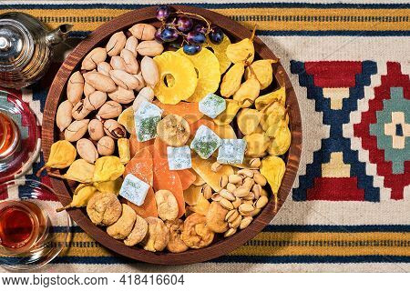 Mix Of Turkish Sweets, Nuts And Dried Fruits - Pears, Figs, Pineapples On Wooden Platter. Glasses Wi