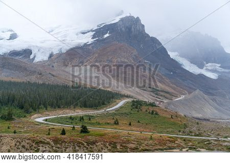 A Narrow Road Climbing Up To The Glaciers Of Columbia Icefield In Canadian Rockies On A Very Cloudy,