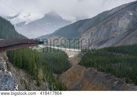 People Walking Around The Columbia Icefield Skywalk On A Cloudy, Rainy Day. Sightseeing In Canadian