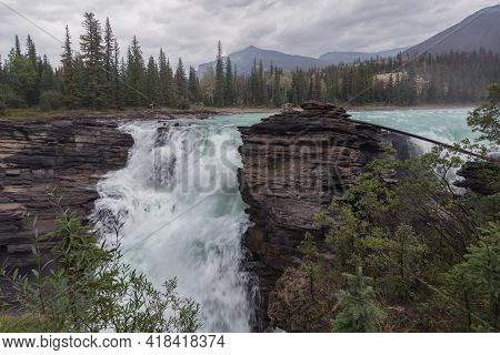 Mighty Athabasca Falls On A Cloudy, Rainy Day In Jasper National Park, Alberta, Canada. Hazy Mountai