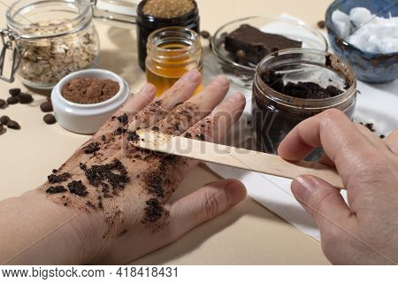 Womans Hands Testing Chocolate Face And Body Scrub. Close Up. Home Beauty Concept.
