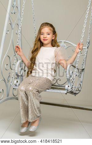 Happy Little Girl Schoolgirl Swinging On A Swing.