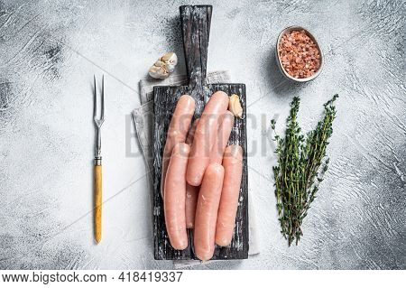 Chicken And Turkey Meat Raw Sausages On A Wooden Board With Thyme. White Background. Top View