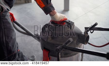 Close-up - Cleaning With A Construction Vacuum Cleaner. Removal Of Dust And Dirt. A Worker Vacuums A