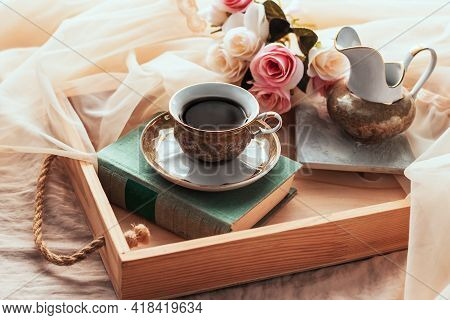 Coffee In Bed, Romantic Morning. A Cup Of Coffee, A Book And A Bouquet Of Flowers On A Wooden Tray O