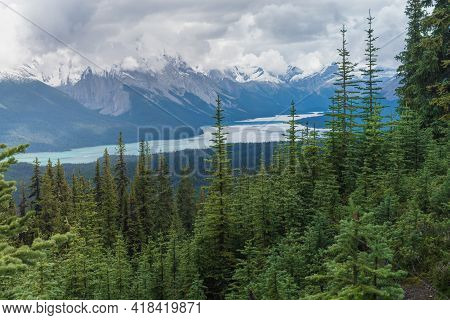 Clouds Gathering Above The Mountain Range In Canadian Rockies. Maligne Lake In Jasper National Park,
