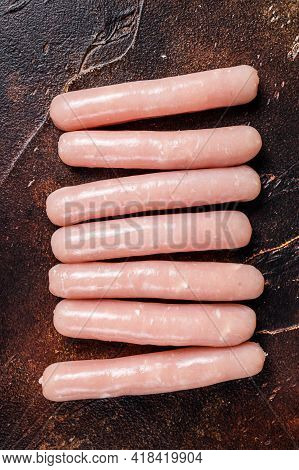 Raw Chicken And Turkey Meat Sausages On Butcher Table. Dark Background. Top View