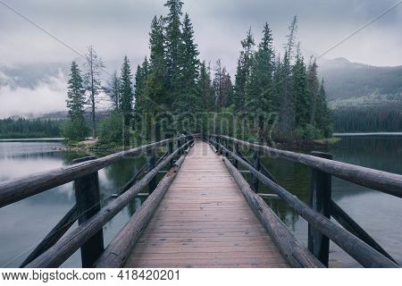 Wooden Bridge Leading To A Small Island In The Background. Pyramid Lake In Canadian Rockies. Misty,