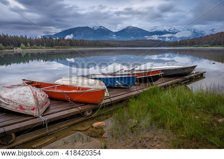 Colorful Boats Sitting On A Wooden Pier On The Shore Of Patricia Lake In Jasper National Park, Alber