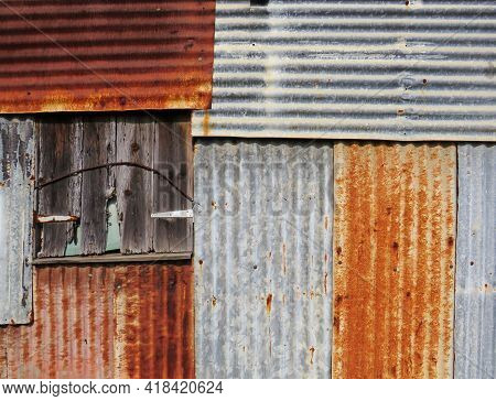Old And Rusty Sheet Metal Facade Background In The French West Indies. Sheet Metal Wall Construction