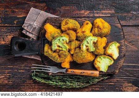 Crumbed Broccoli Steaks On A Wooden Board. Dark Wooden Background. Top View