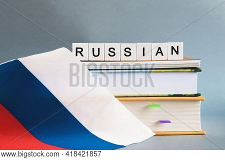 The Inscription Russian On A Stack Of Textbooks, Books, Exercise Books And National Flag Of Russia,