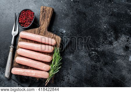 Fresh Raw Chicken And Turkey Meat Sausages On A Wooden Board With Rosemary. Black Background. Top Vi