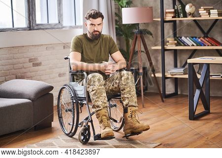 Young Bearded Disabled Veteran Sitting In A Wheelchair And Looking At The Camera
