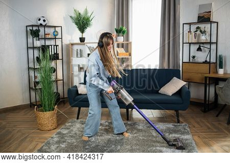 Charming Young Woman In Modern Headphones Enjoying Favorite Music While Cleaning House With Hand Hel