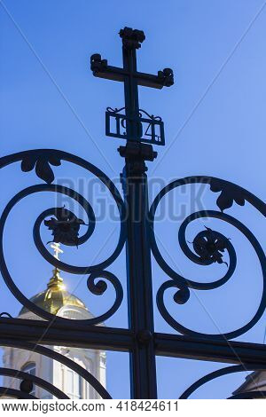 Forged Gate With A Cross At The Entrance To The Cathedral Against The Background Of A Fragment Of A