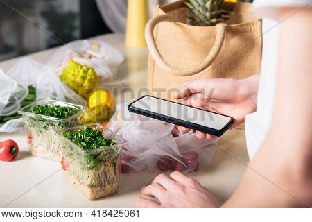 Online Home Food Delivery Of Fresh Vegetables And Fruits. Young Man Holding Phone And Checking Order