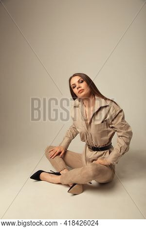 Portrait Of Young Caucasian Brunette Woman In A Beige Blouse Posing On The Floor And Looking At The