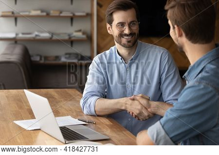 Smiling Business Partners Shake Hands At Team Meeting