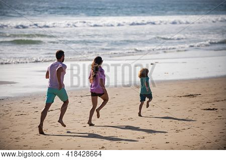 Happy Young Family Run And Jump On Summer Beach. Child With Parents Running And Jumping. Family Trav