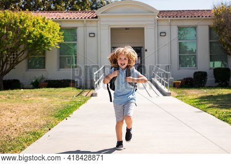 Happy Smiling Kid Is Running To School. Child Boy With Bag Go To Elementary School. Pupil Go Study W