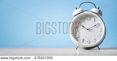 Alarm clock against a blue background with copy space