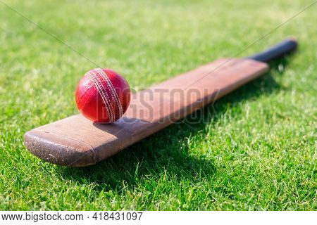 Cricket ball and cricket bat on green grass of cricket ground