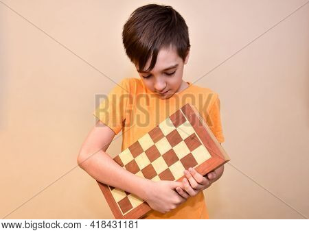 A Boy Holds A Chessboard In His Hands And Looks At It.