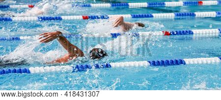 Motion blurred swimmers in a freestyle race, shallow focus on water and water drops, motion blur on swimmer