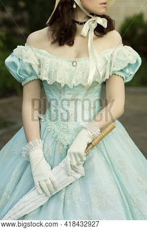 A Beautiful Young Woman In A Historical Blue Dress With An Umbrella, Gloves And A Hat. Dress On A Wo