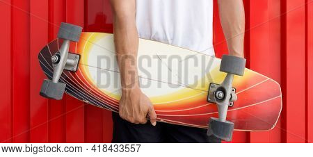 Closeup Man's Hand Holding The Surfskate Board In Hip Position In Front Of Red Galvanized Steel Shee