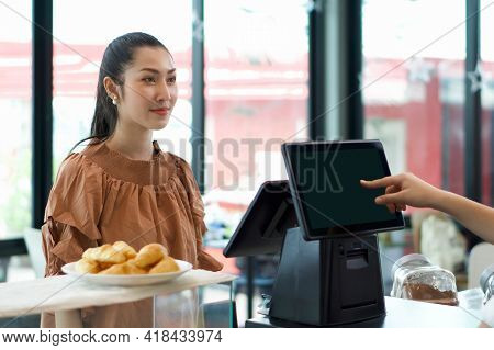 Young Asian Customer Orders A Beverage In Front Of Cashier Counter. Waiter Receive Orders On The Oth