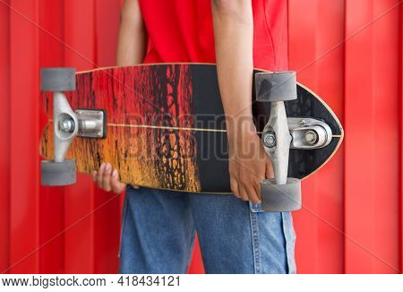 Closeup Surfskates Board In The Hands Of Teenager In A Hip Position.