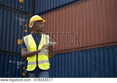 African Worker Holding A Tablet, Walking And Checking The Containers Box From Cargo Ship For Export