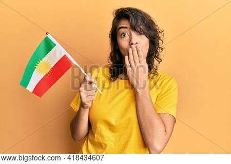 Young hispanic woman holding san fernando flag covering mouth with hand, shocked and afraid for mistake. surprised expression
