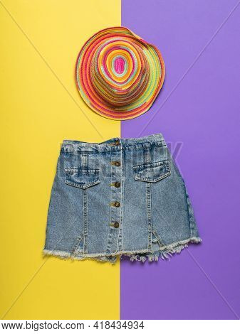 Multi-colored Hat And Denim Skirt On A Yellow And Purple Background. Summer Denim Clothing.
