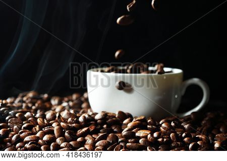 Coffee beans falling in black coffee cup, black background