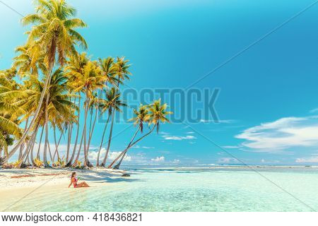 Travel vacation perfect iconic beach with beautiful woman in bikini on private beach island motu relaxing sipping on blue cocktail while sunbathing on French Polynesia travel. Cruise ship destination