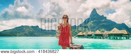Traveling woman walking with luggage in French Polynesia on paradise Motu on Bora Bora with Mount Otemanu. Woman arriving on dream vacation destination
