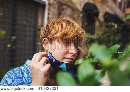The Girl Took Off Her Protective Mask To Sniff The Spring Flowers, A Woman On A Walk Smells Flowerin