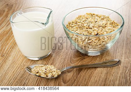 Pitcher With Milk, Transparent Bowl With Raw Oat Flakes, Metallic Spoon With Oat Flakes On Wooden Ta